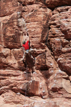 a male rock climber in red leads on a sandstone cliff at Red Rocks, Nevada