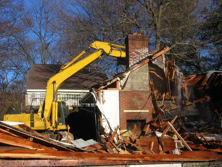 a yellow excavator demolishes a house Stock Photo