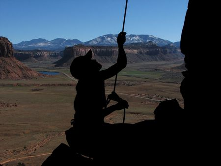 silhouette of a woman rock climber belayer at Indian Creek, Utah Imagens