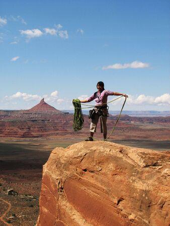 Asian woman rock climber coils the rope after climbing at Indian Creek, Utah Stock Photo - 3615559