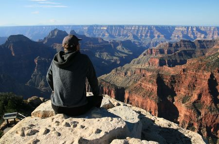 a man sitting on a ledge at Bright Angel point looks over the north rim of the Grand Canyon, Arizona
