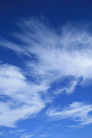 vertical image of blue sky with wispy white  cirrus clouds photo