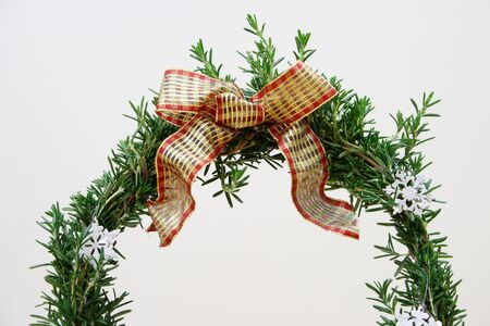 arch of living rosemary with red and gold bow and snowflakes on white Stock Photo - 3659494
