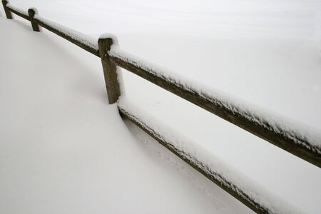 a snow covered wooden fence cuts across a snowy field
