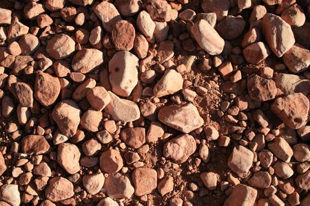 shadowed: red sandstone pebble background in shallow angled evening light