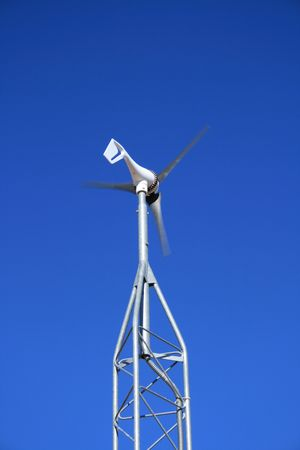 a small electric generating windmill against a blue sky