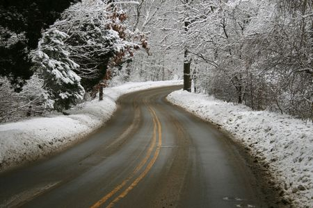 A snowy winter road curves through the snow covered trees Stock Photo - 3659522