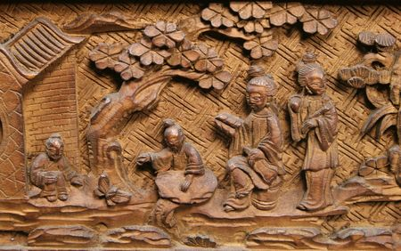Asian carved wood panel with tree, building, and four people Stock fotó