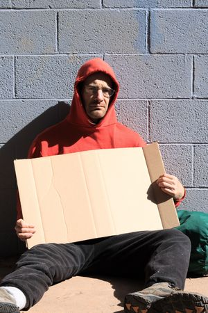 homeless man in red sweatshirt holding a blank cardboard sign