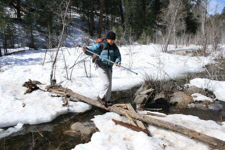 a woman balances across a log over a snow banked stream Stock Photo - 3655671