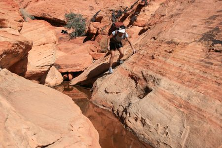 scrambling: Asian woman with backpack scrambling in red rock canyon conservation area, Nevada