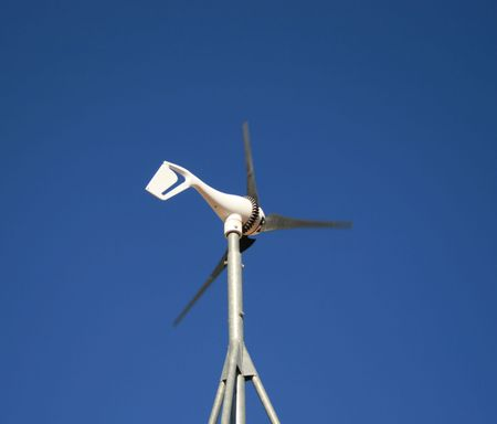 a small electric wind generator against a blue sky