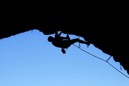rockclimber: silhouette of rock climber climbing on a steep roof