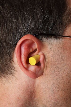 a mans ear with yellow foam earplug