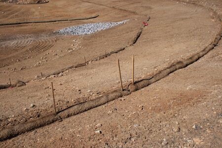 wattle: straw wattle erosion control structure  protects soil and runoff at graded construction site
