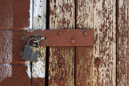 hasp: padlocked hasp on weathered painted brown wood door