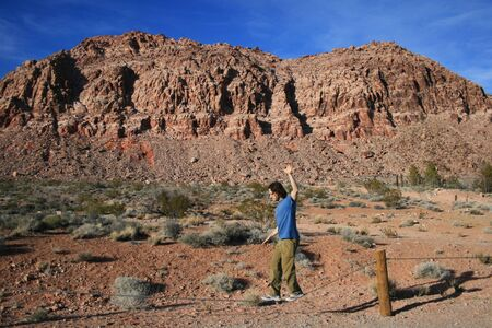 a man balances walking on a cable with red rock scenery Stock Photo - 3687926