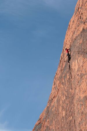 vertical view of a rock climber in red climbing a tall red sandstone cliff at Red Rocks, Nevada Stock Photo - 3687925