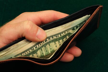 man holding money: a mans hand holds a leather wallet filled with US bills open on a green background  Stock Photo
