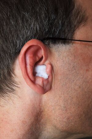 a mans ear with cotton ball earplug