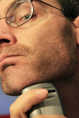 a man shaving his chin with a silver electric razor Stock Photo - 3687947
