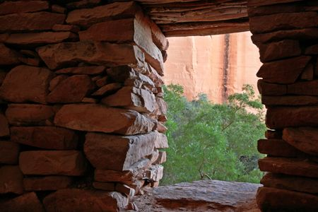 view out of the doorway of an Indian ruin across to the red canyon wall Banco de Imagens