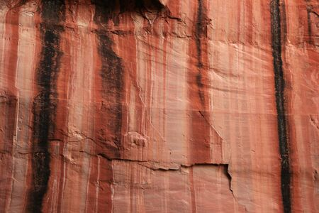 streaked: water streaked red sandstone canyon wall Stock Photo