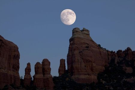 spires: a nearly full moon rises over red rock spires near Sedona, Arizona