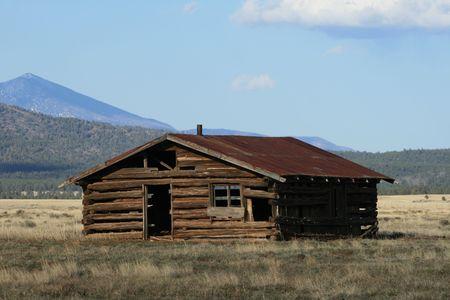 rundown old log cabin in field in northern Arizona
