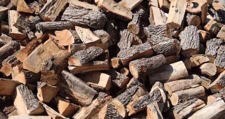 background of randomly piled split firewood logs