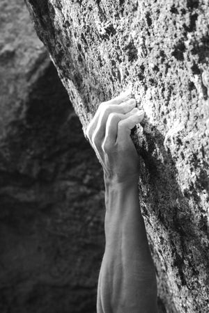 rockclimber: black and white image of a rock climbers hand crimping a small hold Stock Photo