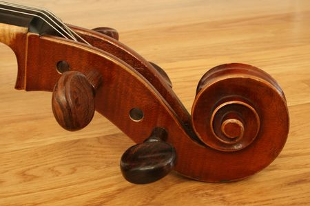 cello scroll and pegboard with tuning pegs on a wooden floor Stock Photo - 3747703
