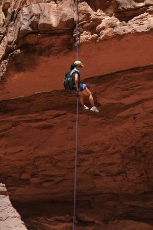 shadowed: canyoneering asian woman rappels into a shadowed canyon in the Grand Canyon National Park