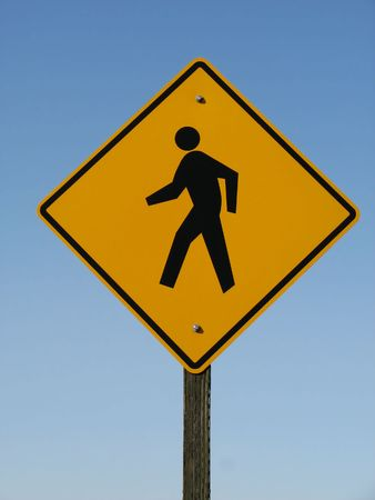 yellow and black pedestrian warning road sign with a blue sky background Stock Photo - 3747682