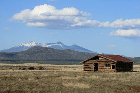 rundown old log cabin in field in northern Arizona with the san francisco peaks in the background Stock Photo - 3747707