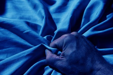 blue image of mans hand grabbing a crumpled striped bed sheet