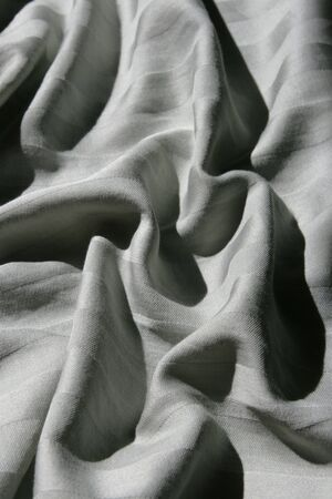 shadowed: vertical image of rumpled striped bed sheet with strong shadows