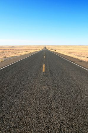 cloudless: highway 180 in Northern Arizona cuts straight across the grasslands to the horizon under a blue sky Stock Photo