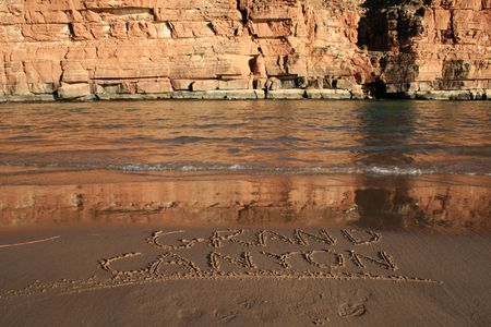 Grand Canyon written in the sand on a Colorado River bank beach across from a cliff Stock Photo - 3863927