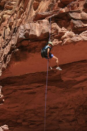 abseil: canyoneering asian woman rappels off a sandstone ledge Stock Photo