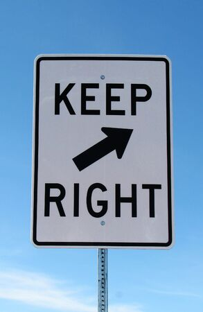 white and black keep right road sign with a blue sky background