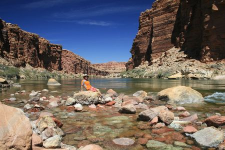 a man in orange sits on a rock in the Colorado River in Marble Canyon Stock Photo - 3854442