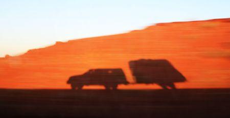 ombra di un eccesso di velocit� e camion rimorchio di viaggio su una mozione offuscata argine di sabbia rossa