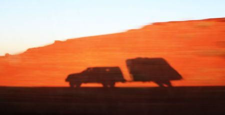 shadow from a speeding truck and travel trailer on a motion blurred red sandy embankment Stock Photo