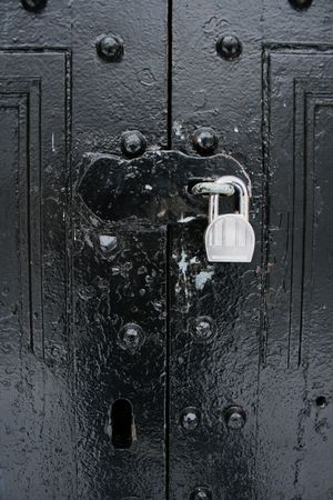 padlocked: vertical image of padlocked hasp on black painted double doors Stock Photo