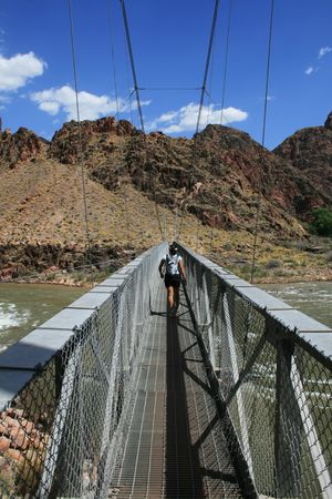 a woman hikes across silver bridge over the Colorado River at the bottom of the Grand Canyon, Arizona Stock Photo - 3859736