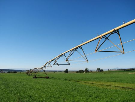 pivot irrigation system in a green field with blue sky copy space