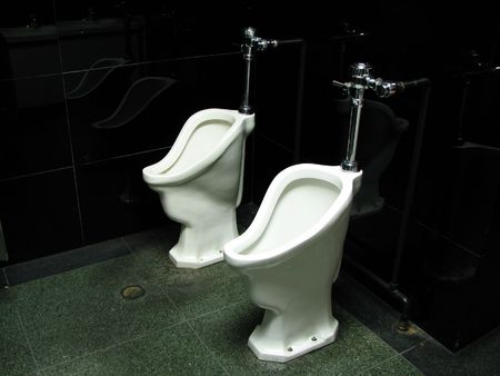urinals in old mens room with black shiny walls photo
