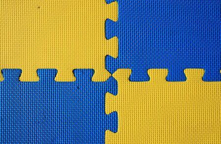 padded: blue and yellow interlocked padded child play mat background Stock Photo