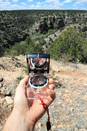a hand holds a compass looking towards a canyon getting a SW bearing
